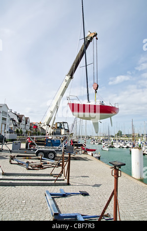 Lifting sailing boat in the water with crane in the harbor - Stock Image
