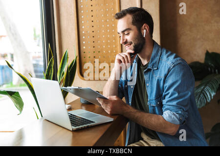 Photo of laughing caucasian man wearing denim shirt using earpod and clipboard with laptop while working in cafe indoors - Stock Image