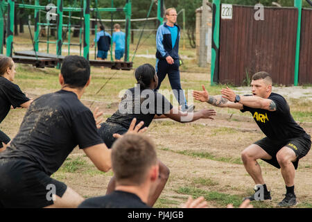 U.S. Soldiers assigned to the 1st Armored Brigade Combat Team, 1st Cavalry Division, participate in morning physical training exercises alongside their Polish counterparts, in Żagań, Poland, Aug. 28, 2018. Soldiers are currently deployed in support of Atlantic Resolve in Europe. (U.S. Army National Guard photo by Pfc. Jacob Hester-Heard, 382nd Public Affairs Detachment, 1ABCT, 1CD/Released) - Stock Image
