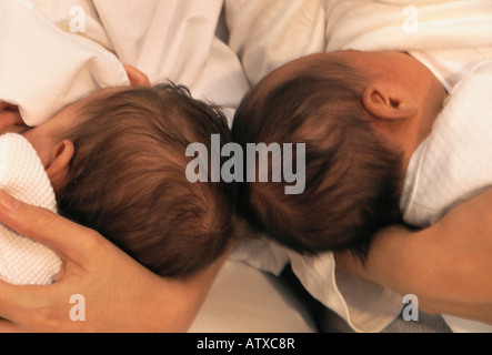 Caucasian mother + Asian mother breastfeeding their side by side infants - Stock Image
