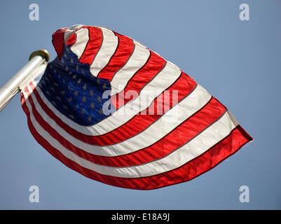Merrick, New York, U.S. - May 26, 2014 - The American flag flies, waving in the wind, during the Merrick Memorial Day Parade and Ceremony, hosted by American Legion Post 1282 of Merrick, honoring those who died in war while serving in the United States military. © Ann E Parry/Alamy Live News Credit:  Ann E Parry/Alamy Live News - Stock Image