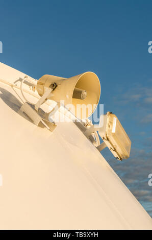 Exterior loudspeaker and lighting fixture mounted on white metal wall of cruise ship. - Stock Image