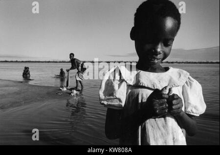 Floods in Mozambique March 2000; a young girl holds two small fish caught by her mother using a piece of cloth as - Stock Image