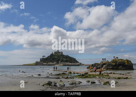 Marazion, Cornwall, UK. 25th May 2019. UK Weather. Despite the sunny hot weather it was a quiet start to the bank holiday weekend at Marazion, with a handful of people wading across the walkway to St Michaels Mount. Credit Simon Maycock / Alamy Live News. - Stock Image