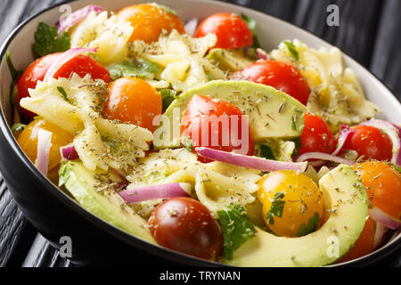 Italian pasta salad farfalle with ripe avocado, onions and tomatoes closeup in a bowl on the table. horizontal - Stock Image