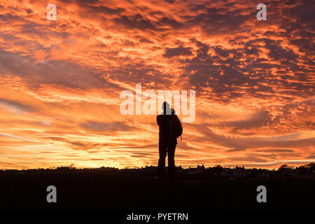 silhouette of man photographing a sunset  - UK - Stock Image
