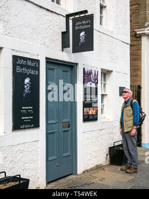Dunbar, East Lothian, Scotland, UK. 21st Apr 2019. John Muir's 181st birthday in his birthplace. The John Muir birthplace museum in the centre of the town. A senior man looking at the signs on the front of the building - Stock Image