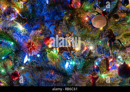 A closeup of decorations and fairy lights on a Christmas tree in England - Stock Image