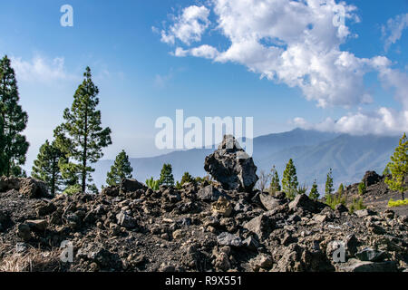 Volcanic rocks looking towards moutain range at Mirador del Llano del Jable, La Palma, Canary Islands - Stock Image