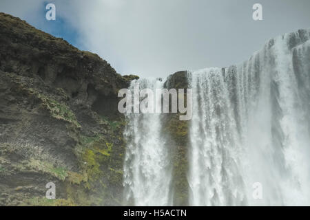 Skogafoss waterfall and rough mossy rock Southerne iceland - Stock Image
