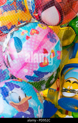 Colourful beach balls decorated with disney cartoon characters in a net for sale, Saronida, Greece. - Stock Image