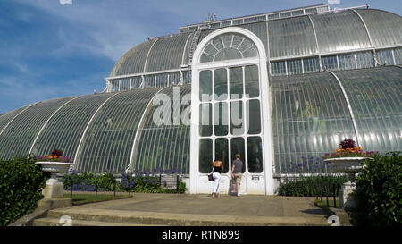 Visitors people at the entrance to the Palm House at the Royal Botanic Garden at Kew Gardens in Richmond, London England UK  KATHY DEWITT - Stock Image