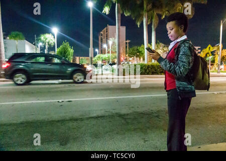 Miami Beach Florida North Beach Collins Avenue Black woman bus stop night reading checking smartphone app schedule estimated time of arrival public tr - Stock Image