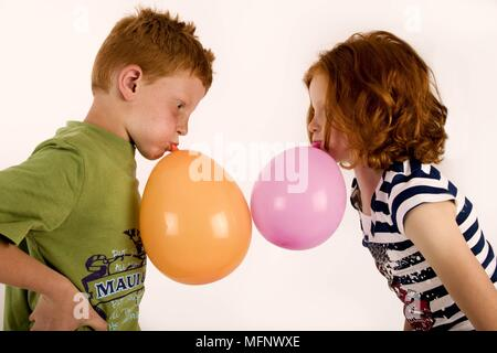 Red haired and freckled twins age7. Blowing up balloons. Studio shot.  Models Released.      Ref: CRB538_103609_0046  COMPULSORY CREDIT: Martin Harvey - Stock Image