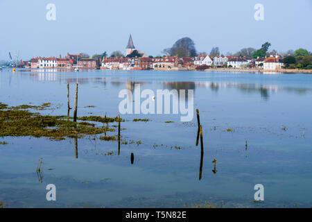 View to pretty old village across Bosham Creek at high tide in Chichester harbour. Bosham, West Sussex, England, UK, Britain - Stock Image