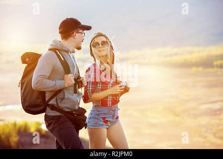 Two young tourists stands and speaks. Travel or trekking concept with couple - Stock Image