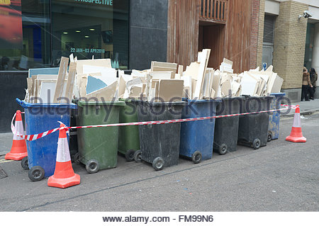 Old sections of plasterboard in wheelie bins, awaiting recycling, in central London, UK. - Stock Image