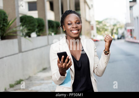 Young businesswoman manifesting her joy when she saw a transfer in her smart phone. - Stock Image