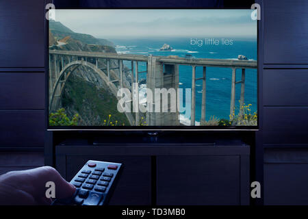 A man points a TV remote at the television which displays the Big Little Lies main title screen (Editorial use only). - Stock Image