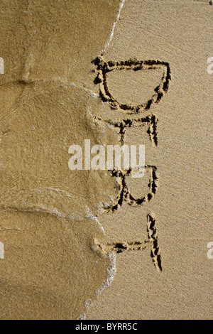 'Debt' written out in wet sand, being washed away by the sea. Please see my collection for more similar - Stock Image