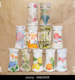 Decoupaged jars arranged in a triangular manner. Jars have different decorative motifs. One of the jars has written on it word Flowers in French. - Stock Image