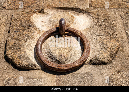 Rusty metal mooring ring set in stone on the quayside - Stock Image