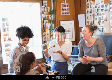 Creative female designers eating sushi in office - Stock Image