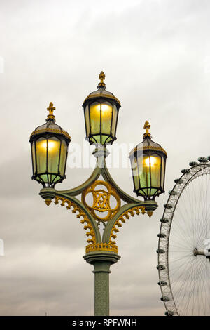 Ornate triple headed cast iron  lamp post with lights lit on Westminster Bridge  England London with the London eye in the background - Stock Image