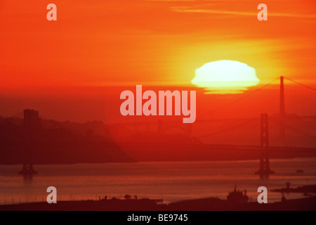 Sunset behind Bay Bridge & Golden Gate Bridge in San Francisco Bay, CA, USA - Stock Image