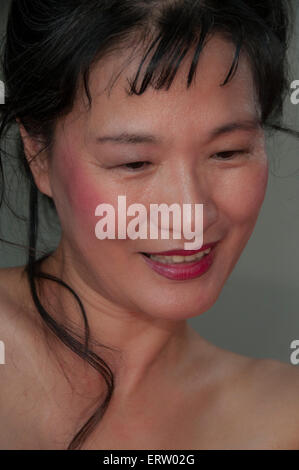 Mature Asian woman with beautiful complexion, looking down and away from camera - Stock Image