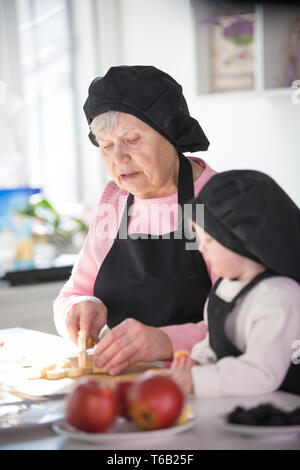 An old woman with a little girl in the kitchen. Cutting a banana - Stock Image