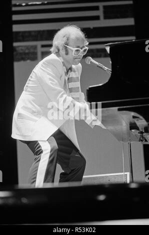 Elton John performing on stage, during the Elton John and Ray Cooper concert tours. Rainbow Theatre, London. 2nd May 1977. - Stock Image