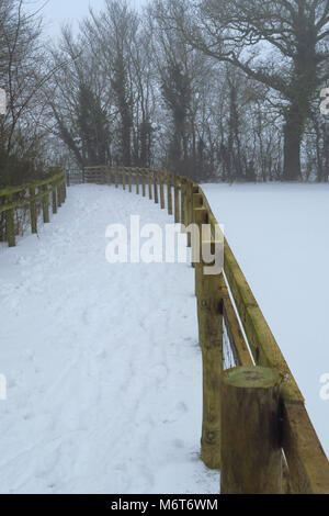 Snow covered footpath in the north Oxfordshire village of Hook Norton - Stock Image