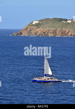 catamaran with passengers near Caribbean island surrounded by blue water - Stock Image