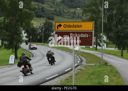 Olden, Norway - 8 August 2018: Two motorcyclists ride into the village of Olden on 8 August 2018.  The village of about 500 inhibitions engage in agriculture, fruit growing and manufacture for tourism is a few miles to Briksdalebreen Glacier. Photo: David Mbiyu - Stock Image