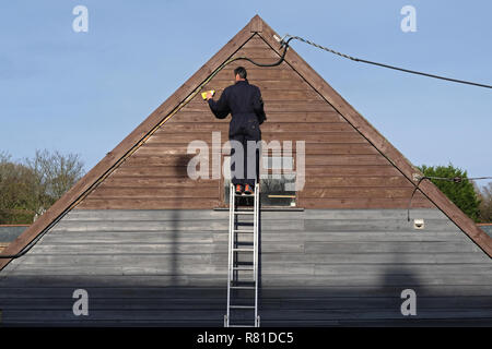A carpenter, decorator, sanding down the exterior woodwork of a building. - Stock Image