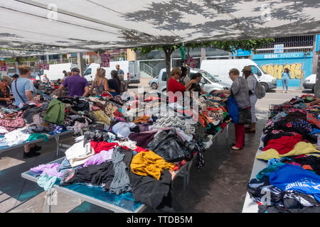 Piles of clothes for browsing in a sale at a local spanish clothes market - Stock Image