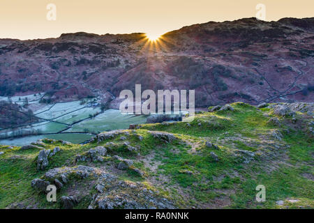 Sunset behind the ridsge of Little Castle How and Great Castle How, seen from Helm Crag, Grasmere, Lake District, Cumbria - Stock Image