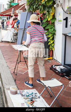 Singapore - 22nd December 2018: Artist painting watercolour on Arab Street. This is in the Kampong Glam area - Stock Image