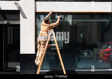 Workman on a ladder making a repair with a cordless power drill - Stock Image