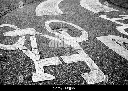 pedestrian crossing accross curved bicycle asphalt line, high contrast photo - Stock Image