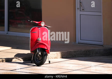An old red Vespa scooter parked on a stand on the street. Despite its age the scooter is in good condition and bright - Stock Image