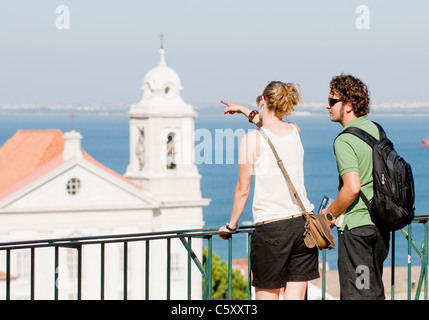 A male and female tourist admiring the views and São Miguel church from Largo das Portas do Sol in Alfama, - Stock Image