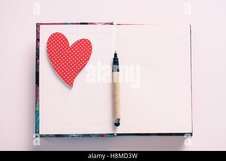 Love heart on notebook with pen - Stock Image