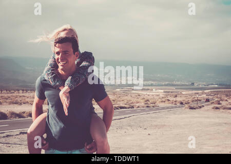 Relationship concept with young caucasian people cheerful happy couple enjoying the outdoor leisure activity together - man smile and carry woman on h - Stock Image