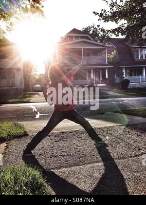 Boy playing in yard with flair from sun. - Stock Image