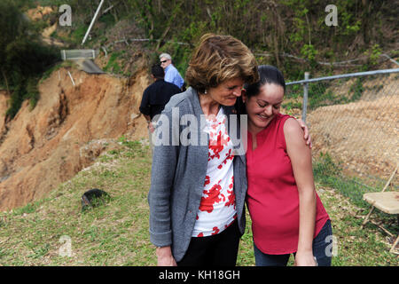 U.S. Alaska Senator Lisa Murkowski (left) meets with Puerto Rican residents at the site of a large landslide during - Stock Image