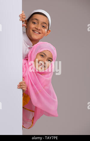 Young Muslim girl and boy peeking out from behind the wall - Stock Image
