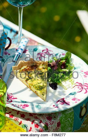 A piece of cheese quiche with a mixed leaf salad on a garden table - Stock Image