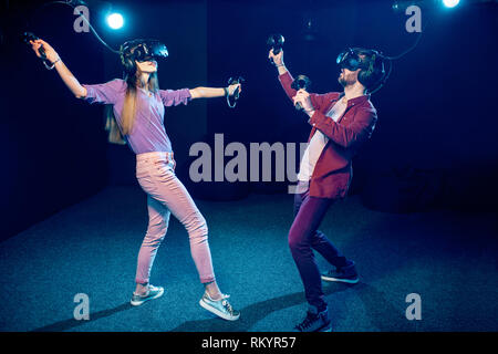 Man and woman playing game using virtual reality headset and gamepads in the dark room of the playing club - Stock Image